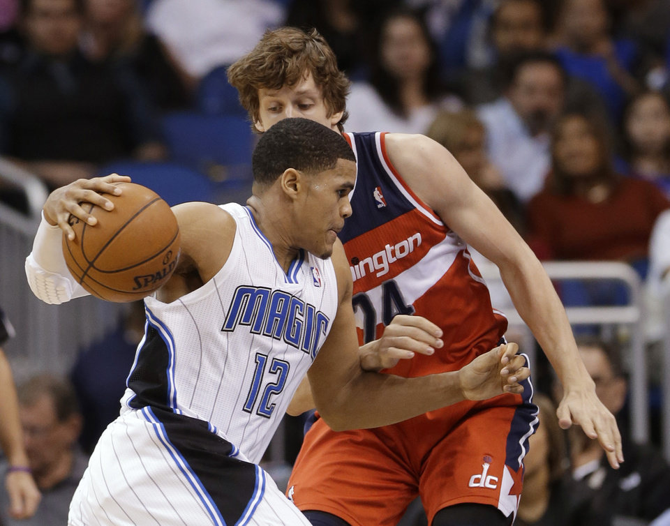 Orlando Magic's Tobias Harris (12) drives around Washington Wizards' Jan Vesely, of the Czech Republic, during the first half of an NBA basketball game, Friday, March 29, 2013, in Orlando, Fla. (AP Photo/John Raoux)