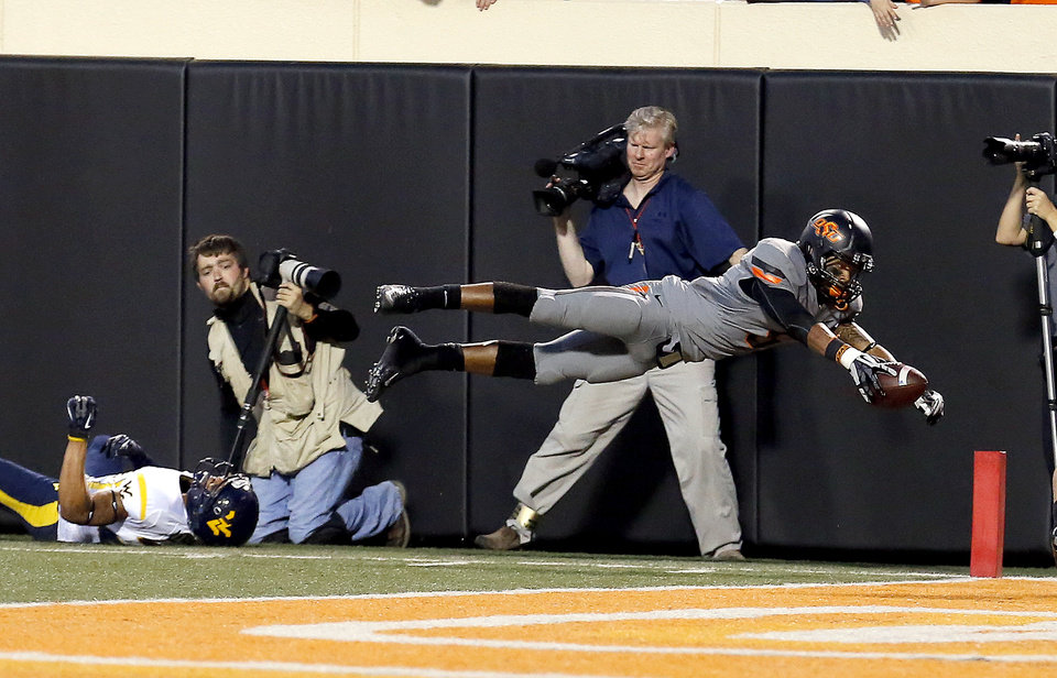 Photo - Oklahoma State's Josh Stewart (5) dives for a touchdown in front of West Virginia's Cecil Level (24) in the fourth quarter  during a college football game between Oklahoma State University (OSU) and the West Virginia University at Boone Pickens Stadium in Stillwater, Okla., Saturday, Nov. 10, 2012. Photo by Sarah Phipps, The Oklahoman