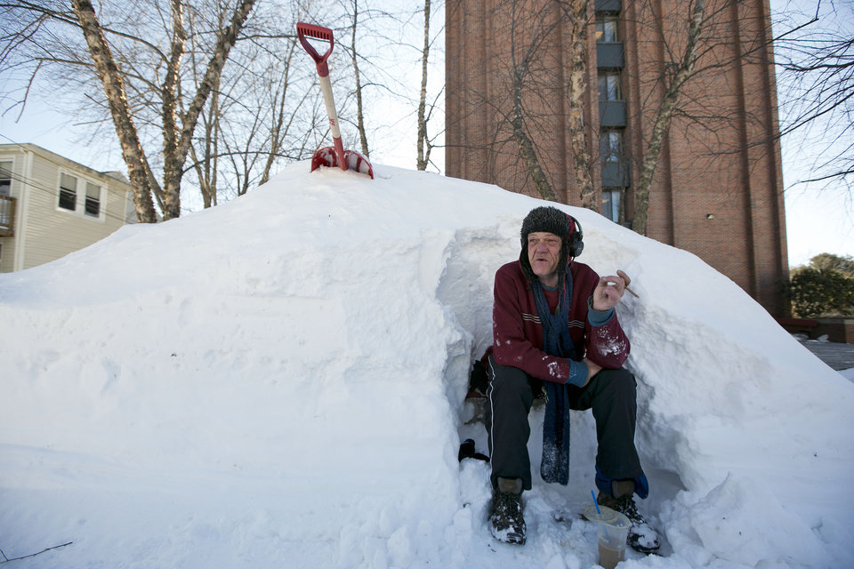 Photo - Bert Johnson takes a break while clearing snow from a bus-stop bench outside the apartment complex where he lives in Portland, Maine, Sunday, Feb. 10, 2013. Residents are digging out after a blizzard dumped a record 31.9 inches of snow on the city. (AP Photo/Robert F. Bukaty)