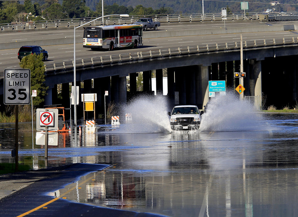 A truck drives through flooding from bay waters at a Highway 1 off ramp in Marin County, Calif. on Wednesday, Dec. 12, 2012. Highway 101 is in background. Forecasters are urging people enjoying the Northern California coast to be careful as high tides and big waves hit the region's beaches during the next few days. The National Weather Service says so-called King Tides — caused by a rather unique combination of how the sun, the moon and the earth align — will bring the highest tides of the year on Thursday, Friday and Saturday mornings. (AP Photo/San Francisco Chronicle, Brant Ward)  NORTHERN CALIFORNIA MANDATORY CREDIT PHOTOG & CHRONICLE; MAGS OUT; NO SALES;