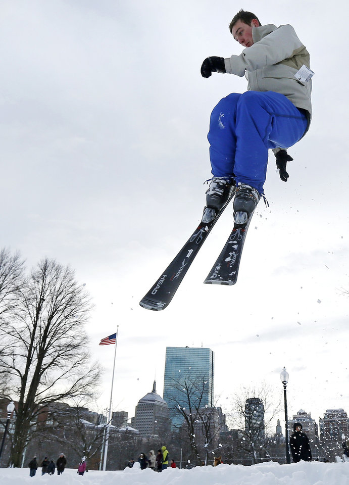 Thomas Kolek, a Northeastern University student from Westford, Mass., spins a helicopter jump while skiing on Boston Common in Boston, Saturday, Feb. 9, 2013.  The Boston area received about two feet of snow from a winter storm. A howling storm across the Northeast left the New York-to-Boston corridor shrouded in 1 to 3 feet of snow Saturday, stranding motorists on highways overnight and piling up drifts so high that some homeowners couldn't get their doors open. More than 650,000 homes and businesses were left without electricity. (AP Photo/Charles Krupa)