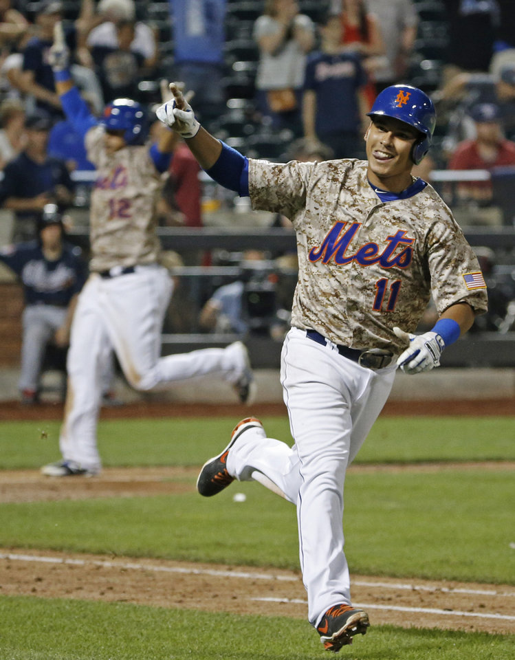 Photo - New York Mets Juan Lagares (12), left,  celebrates as he scores on Ruben Tejada's 11th inning game-winning, walk-off, RBI single in a baseball game against the Atlanta Braves in New York, Monday, July 7, 2014. The Mets defeated the first place Braves, 4-3. (AP Photo/Kathy Willens)