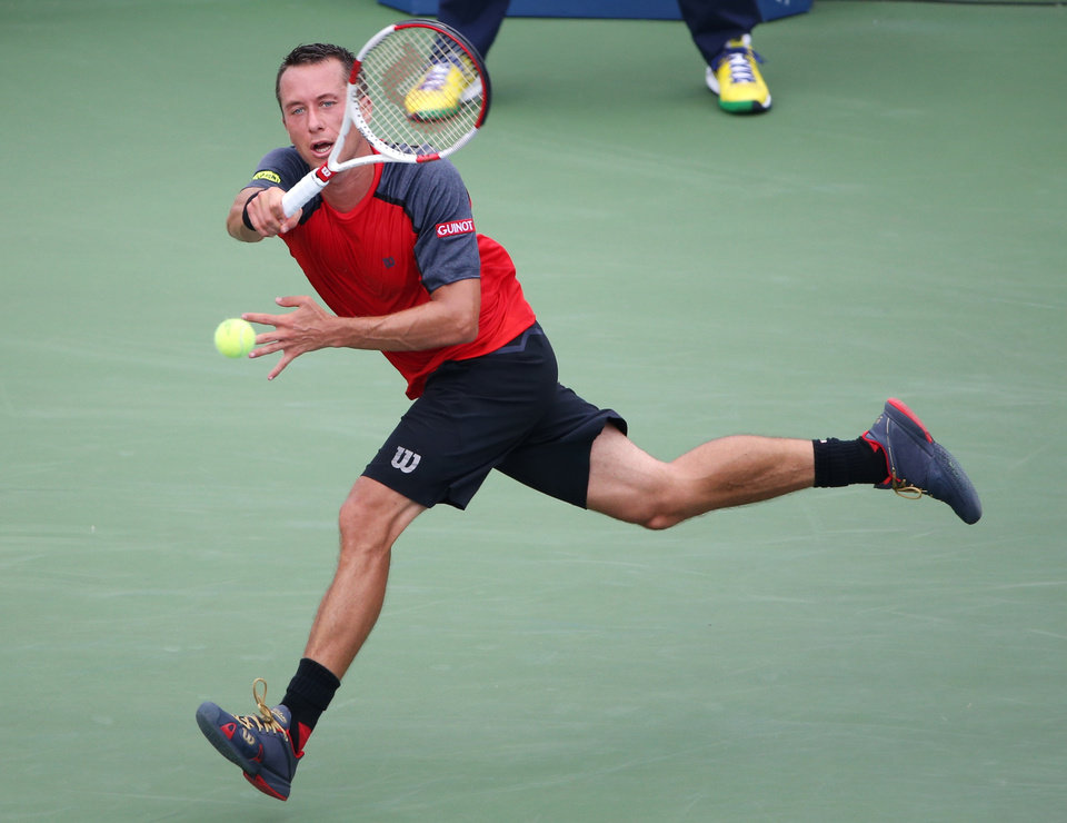 Photo - Philipp Kohlschreiber, of Germany, returns a shot against Novak Djokovic, of Serbia, during the fourth round of the 2014 U.S. Open tennis tournament, Monday, Sept. 1, 2014, in New York. (AP Photo/John Minchillo)