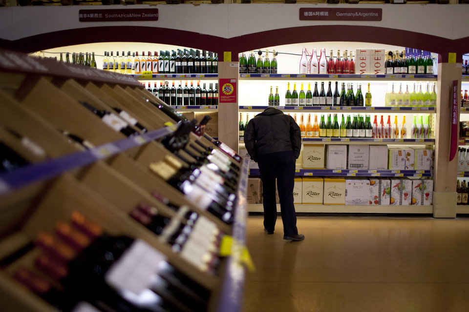 "ADVANCE FOR MONDAY, DEC. 3. - In this Nov. 27, 2012 photo, a customer checks bottles of imported wine at a supermarket in Beijing, China. Rising incomes have driven demand for wine and other luxury goods, making China a lifeline for European and American vineyards when the global crisis battered traditional markets. The Chinese have ""helped Bordeaux a lot these past three years,"" said Florence Cathiard, owner of Chateau Smith Haut Lafitte in the Pessac-Leognan area of France's southwest, home of high-end Bordeaux wine. (AP Photo/Alexander F. Yuan)"