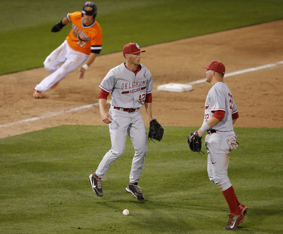Photo - The ball lands between OU's Drew Krittenbrink, center, and Sheldon Neuse as OSU's Gage Green advances to third in the 8th inning of a Bedlam baseball game between Oklahoma State University and the University of Oklahoma in Stillwater, Tuesday, April 15, 2014. Photo by Bryan Terry, The Oklahoman