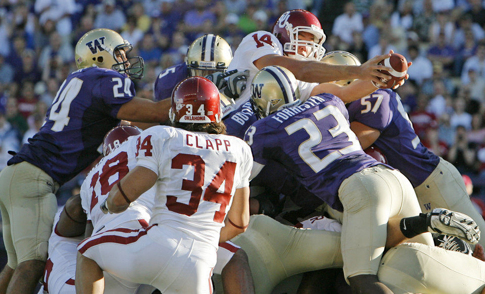 Photo - OU quarterback Sam Bradford (14) extends the ball over the pile for a rushing touchdown in the second quarter during the college football game between Oklahoma and Washington at Husky Stadium in Seattle, Wash., Saturday, September 13, 2008. BY NATE BILLINGS, THE OKLAHOMAN