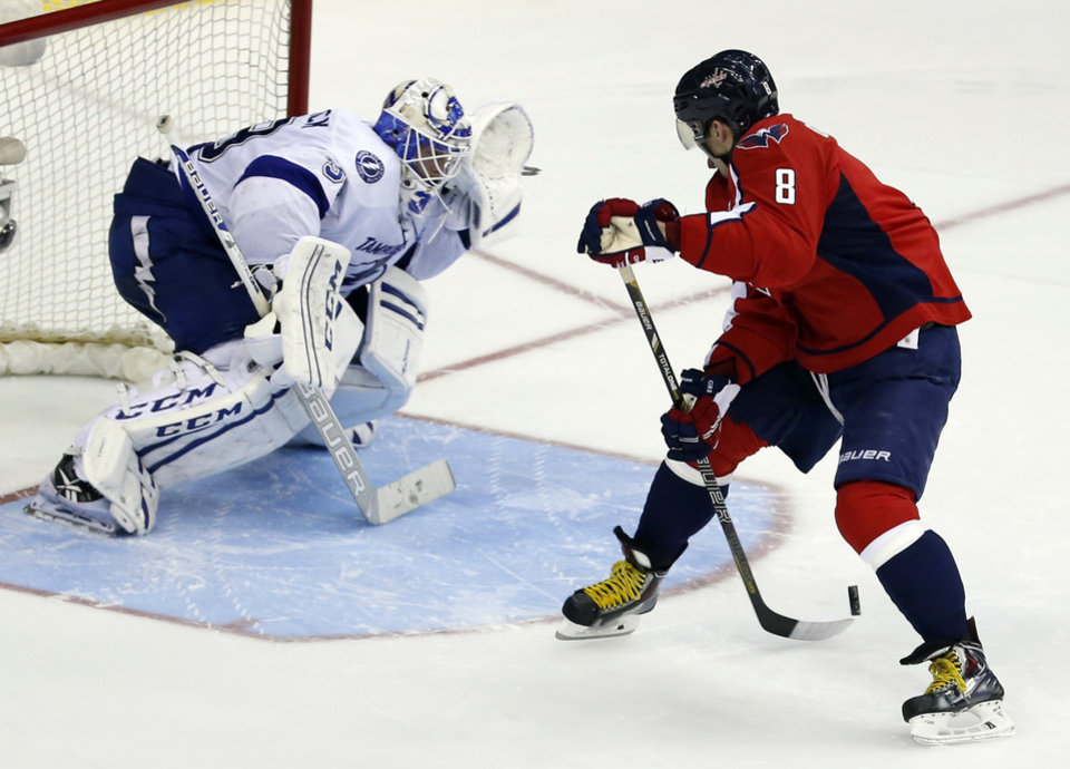 Photo - Washington Capitals right wing Alex Ovechkin, right, from Russia, shoots the puck behind his back against Tampa Bay Lightning goalie Anders Lindback, from Sweden, in the shootout portion of an NHL hockey game on Sunday, April 13, 2014, in Washington. Lindback blocked the shot and the Lightning won 1-0 in a shootout. (AP Photo/Alex Brandon)