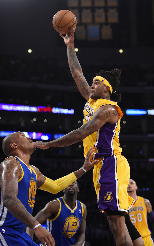 Photo - Los Angeles Lakers forward Jordan Hill shoots as Golden State Warriors forward Marreese Speights defends during the first half of an NBA basketball game, Friday, April 11, 2014, in Los Angeles. (AP Photo/Mark J. Terrill)