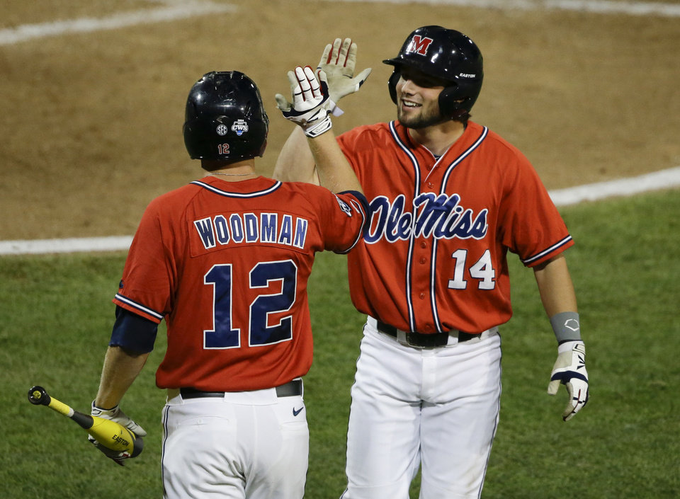 Photo - Mississippi's Cameron Dishon (14) exchanges high-fives with J.B. Woodman (12) after Dishon scored an equalizing run against Virginia in the eighth inning of an NCAA baseball College World Series game in Omaha, Neb., Sunday, June 15, 2014. (AP Photo/Nati Harnik)