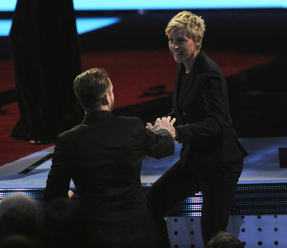 Photo - Justin Timberlake, left, congratulates Ellen DeGeneres, winner of the favorite daytime TV host award, as she walks on stage at the 40th annual People's Choice Awards at the Nokia Theatre L.A. Live on Wednesday, Jan. 8, 2014, in Los Angeles. (Photo by Chris Pizzello/Invision/AP)