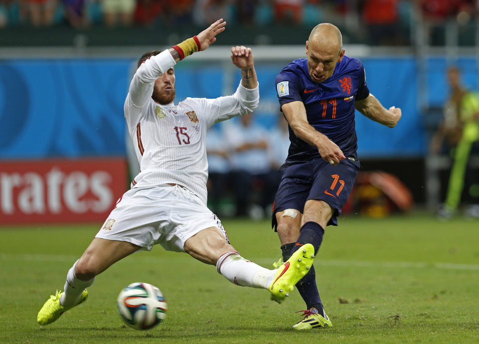 Photo - Netherlands' Arjen Robben kicks the ball past Spain's Sergio Ramos to score his side's second goal during the second half of the group B World Cup soccer match between Spain and the Netherlands at the Arena Ponte Nova in Salvador, Brazil, Friday, June 13, 2014. (AP Photo/Wong Maye-E)
