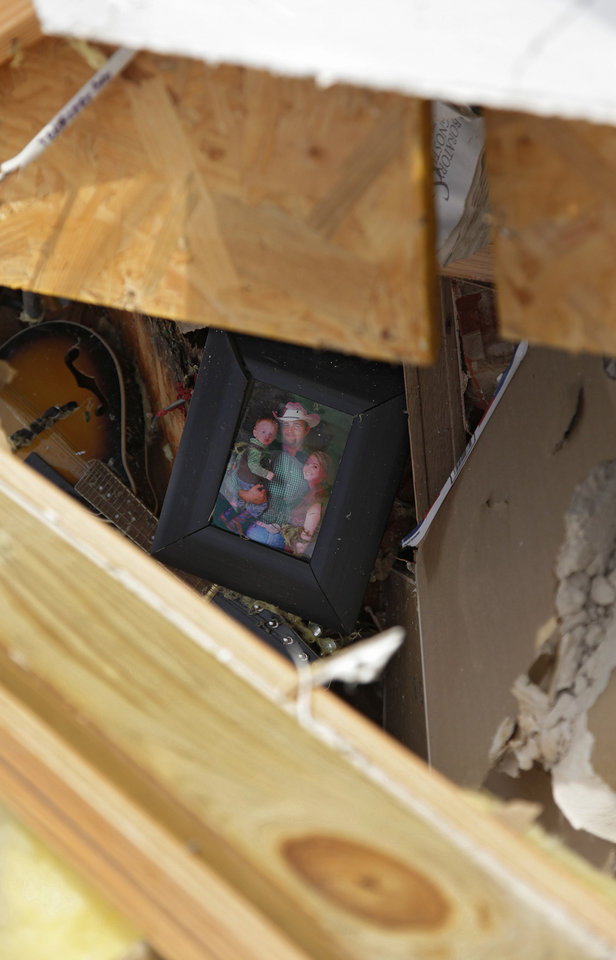 Photo - A family photo made it through the storm after a tornado destroyed the home of Tom and M'Lynn McCann west of El Reno, Tuesday, May 24, 2011. Photo by Chris Landsberger, The Oklahoman ORG XMIT: KOD