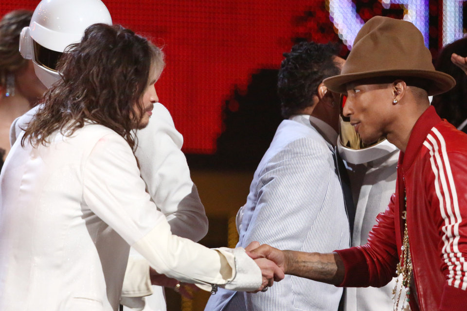 Photo - Steven Tyler, left, presents Pharrell Williams with the award for record of the year at the 56th annual Grammy Awards at Staples Center on Sunday, Jan. 26, 2014, in Los Angeles. (Photo by Matt Sayles/Invision/AP)