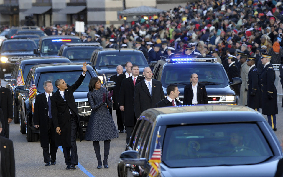 Photo - President Barck Obama and first lady Michelle Obama walk in the Inaugural Parade after the ceremonial swearing-in for the 57th Presidential Inauguration on Capitol Hill in Washington, Monday, Jan. 21, 2013. (AP Photo/Susan Walsh)