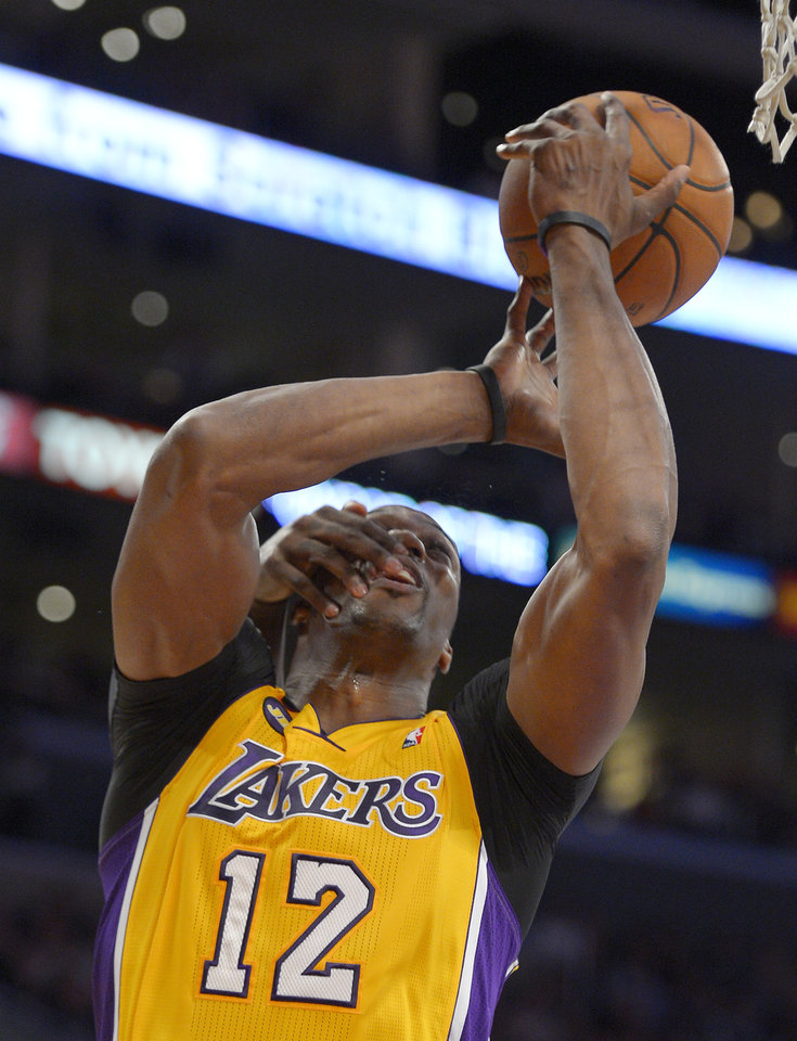 Photo - Los Angeles Lakers center Dwight Howard is slapped in the face by Portland Trail Blazers center J.J. Hickson during the first half of their NBA basketball game, Friday, Feb. 22, 2013, in Los Angeles. (AP Photo/Mark J. Terrill)