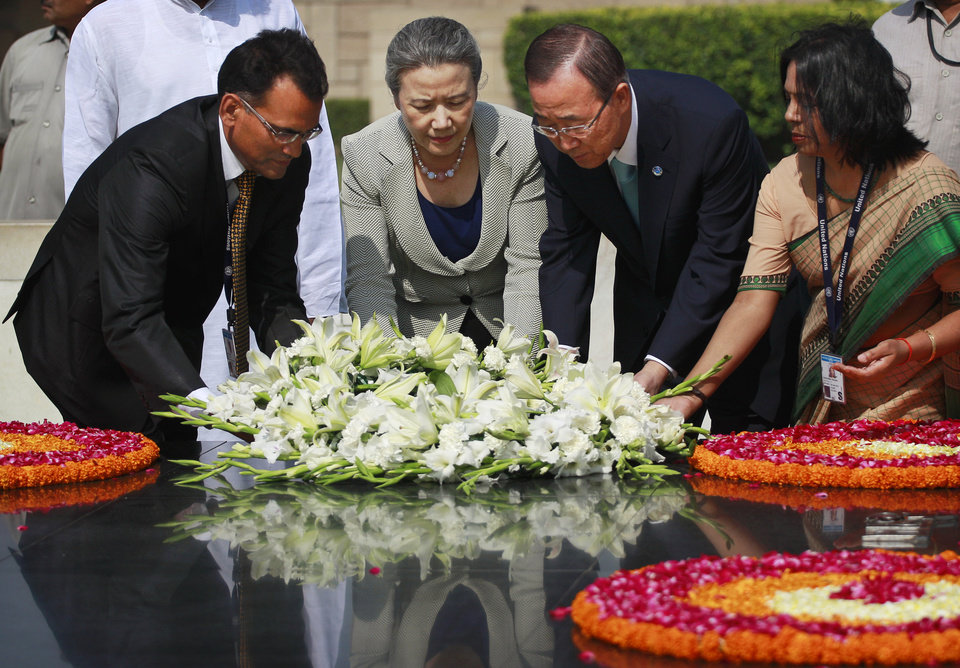 Photo -   U.N. Secretary-General Ban Ki-moon, center right, and wife Yoo Soon-taek, center left, place a wreath as they pay respects at Rajghat, the memorial to the late Mahatma Gandhi in New Delhi, India, Friday, April 27, 2012. Ban is on a three day official visit to India. (AP Photo/Kevin Frayer)