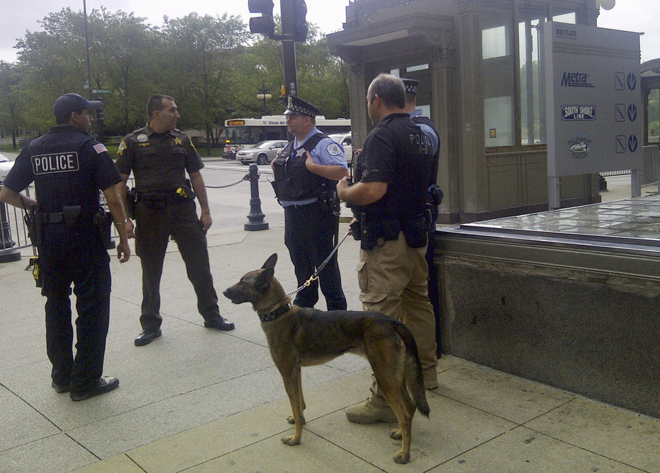 Photo -   Chicago police officers with a police dog stand outside the Metra commuter line's Millennium Station near Chicago's Grant Park Monday morning, May 21, 2012. Commuter traffic appears to be down in Chicago as the NATO summit enters its second and final day. Many companies heeded official advice and are letting their workers stay home for the day. (AP Photo/Ryan J. Foley)
