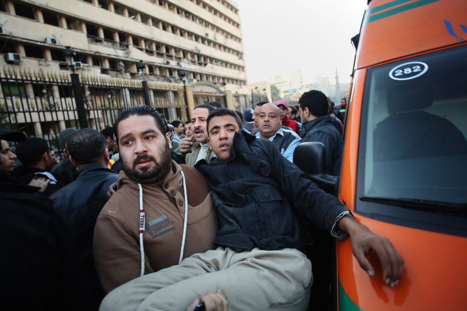 Photo - A man carries an Egyptian police officer to an ambulance after a blast at the Egyptian police headquarters in downtown Cairo, Friday, Jan. 24, 2014. A car bomb struck the Egyptian police headquarters in downtown Cairo on Friday, killing at least several people and wounding dozens, the country's state media reported. (AP Photo/Khalil Hamra)