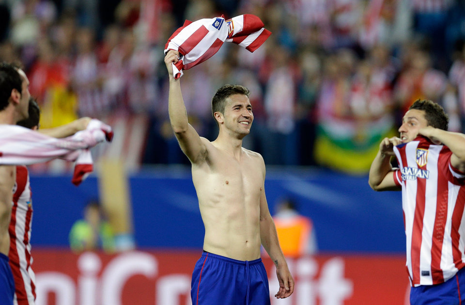 Photo - Atletico's Gabi, center, celebrates at the end of the Champions League quarterfinal second leg soccer match between Atletico Madrid and FC Barcelona in the Vicente Calderon stadium in Madrid, Spain, Wednesday, April 9, 2014. Atletico defeated Barcelona 1-0. (AP Photo/Paul White)