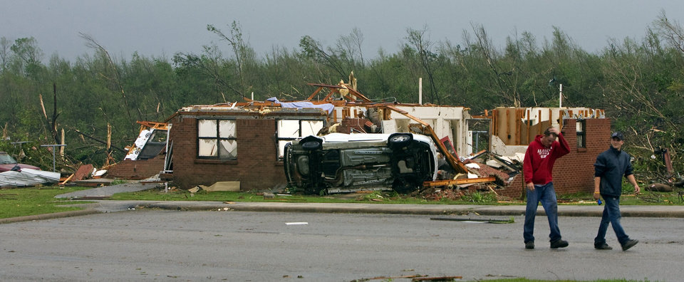 Photo - Michael Sexton and friend T.J, Wilson walk through part of the public housing after a tornado struck Wednesday, April 27, 2011 in Phil Campbell, Ala.  (AP Photo/TimesDaily, Daniel Giles)