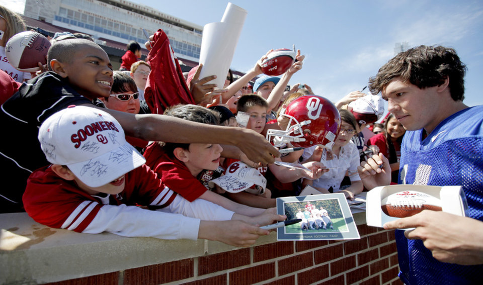 Photo - OU quarterback Sam Bradford is mobbed by fans wanting autographs after the Sooners' Red-White game in April. (Photo by Bryan Terry, The Oklahoman)