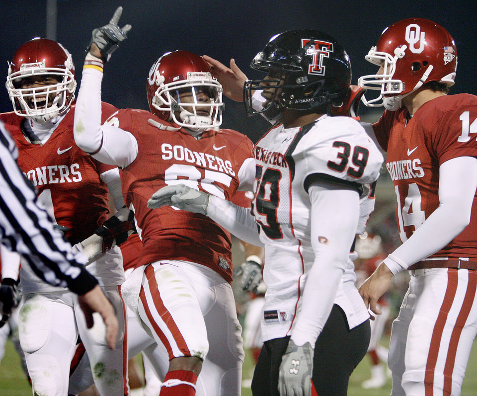Photo - OU's Manuel Johnson, left, Ryan Broyles, and Sam Bradford celebrate in front of Eli Ferguson of Texas Tech after a touchdown during the college football game between the University of Oklahoma Sooners and Texas Tech University at Gaylord Family -- Oklahoma Memorial Stadium in Norman, Okla., Saturday, Nov. 22, 2008. BY BRYAN TERRY, THE OKLAHOMAN