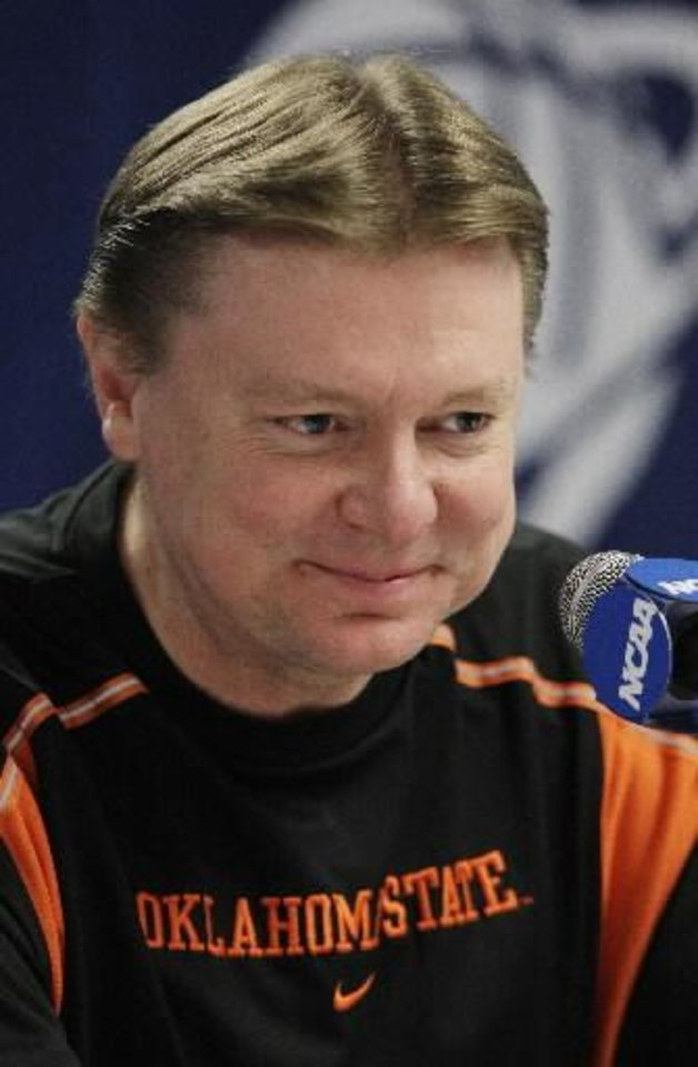 Photo - In this March 21, 2010 file photo, Oklahoma State women's basketball head coach Kurt Budke grins during a news conference in Tempe, Ariz. Oklahoma State University says Budke and assistant coach Miranda Serna were killed in a plane crash in central Arkansas. The university said in a news release Friday, Nov. 18, 2011 that the two were on a recruiting trip to Arkansas when the plane crashed near Perryville, about 45 miles west of Little Rock. (AP Photo/Ross D. Franklin, File)
