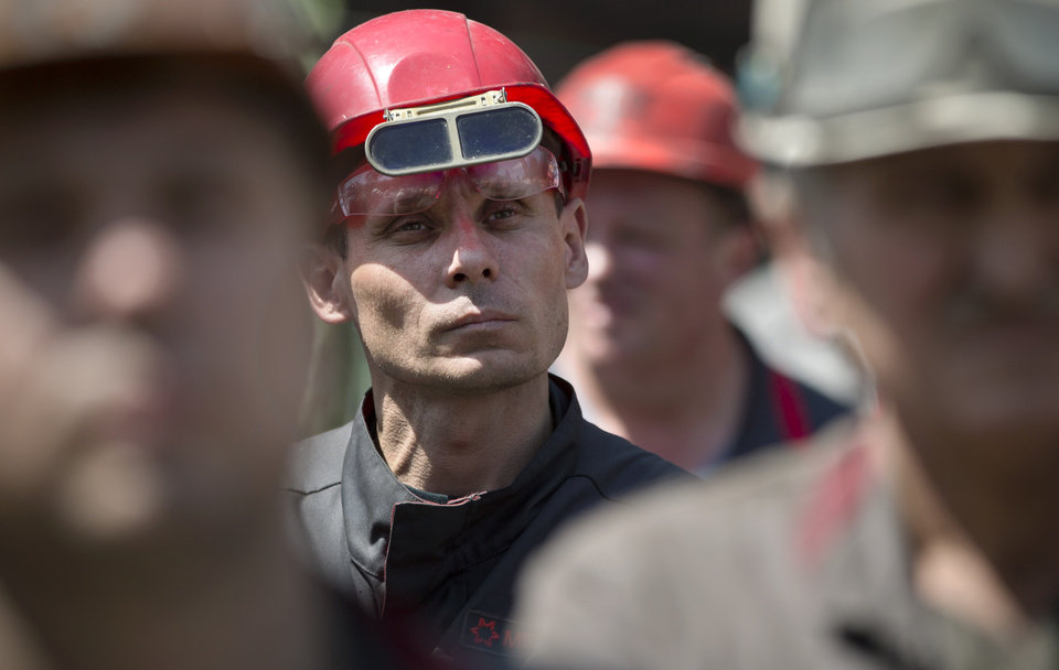 Photo - Workers of Illich Iron & Steel Works steel plant stand during an anti-war protest, supported by the management, in Mariupol, eastern Ukraine, Thursday, May 22, 2014. Ukrainian metals tycoon Rinat Akhmetov, riding a wave of public dismay with the fighting, issued a strong call against the mutiny in the east, which he described as a fight against the citizens of the region that has devastated Ukraine's industrial heartland.(AP Photo/Vadim Ghirda)