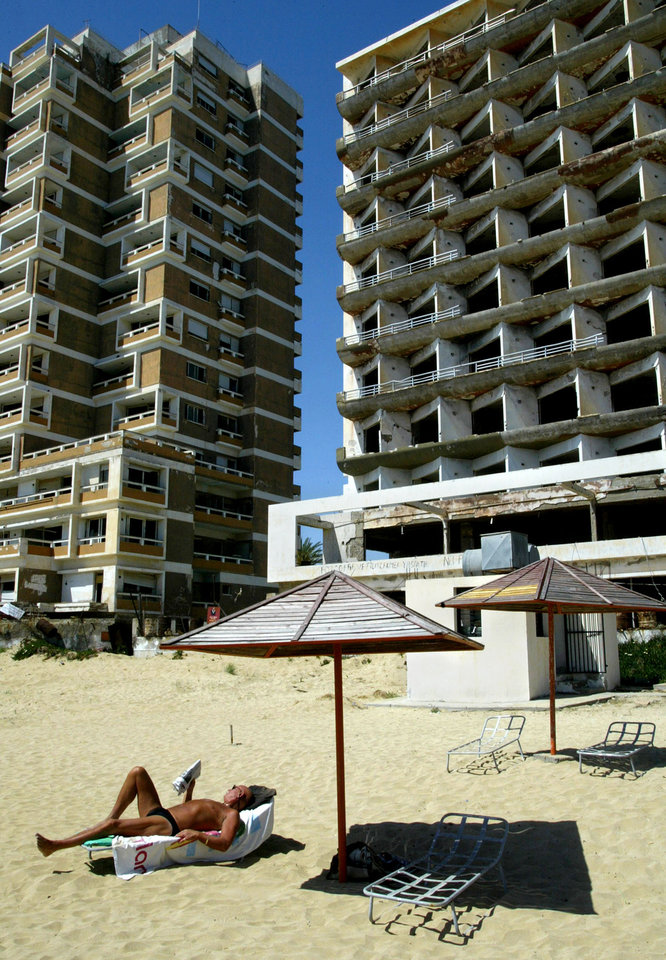 Photo - FILE - In this Monday, May 5, 2003 file photo, a tourist reads his book as he sunbathes in front of a destroyed hotel in the Turkish-occupied of abandoned coastal city of Varosha, in southeast of the island of Cyprus. Time virtually stopped in 1974 for the Mediterranean tourist playground of Varosha. When Turkey invaded Cyprus in the wake of a coup by supporters of union with Greece, thousands of residents fled, and chain-link fences enclosed a glamorous resort that it's said once played host to Hollywood royalty like Elizabeth Taylor.  (AP Photo/Petros Karadjias, file)