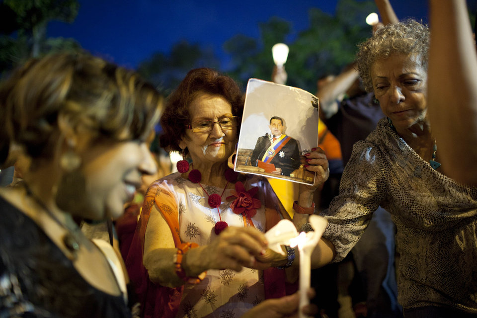 A woman holds a picture of Venezuela's President Hugo Chavez as she lights a candle during a vigil to pray for Chavez's health as he remains in a hospital undergoing cancer treatment in Caracas, Venezuela, Friday, Feb. 22, 2013. Government officials have said Chavez is breathing through a tracheal tube, but they have also shown a few letters and other documents with his signature. (AP Photo/Ariana Cubillos)