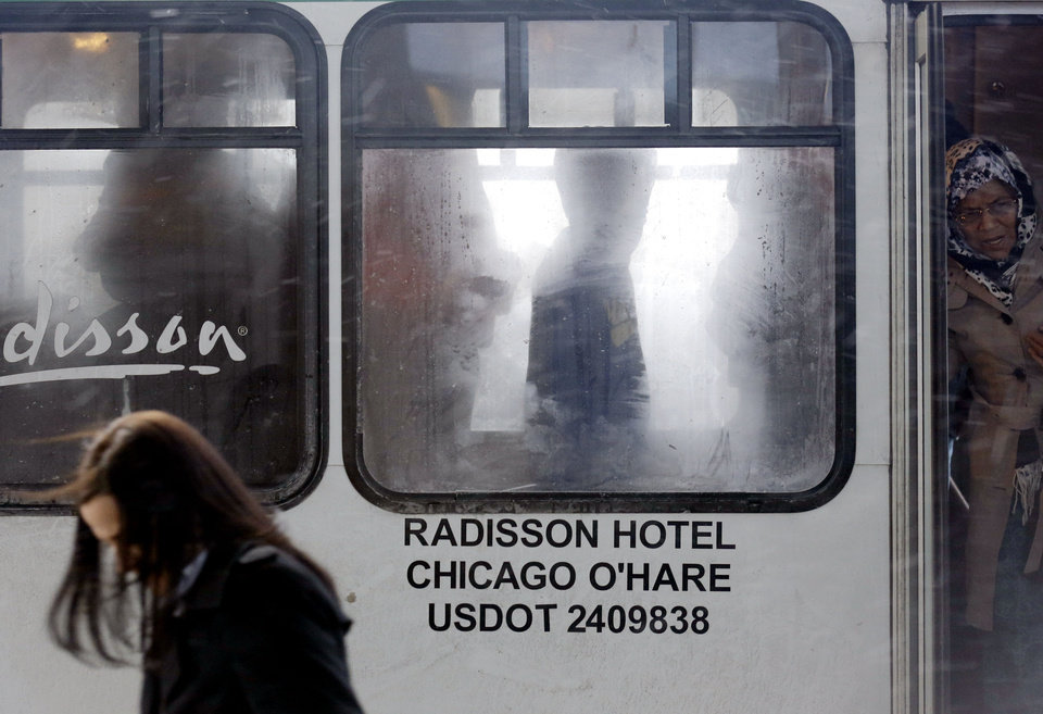 Photo - Travelers get off a Radisson hotel shuttle bus at O'Hare International Airport in Chicago on Sunday, Jan. 5, 2014. Illinois residents are digging out of more snow and preparing for bitterly cold temperatures. Sunday night temperatures are predicted to drop drastically, to about minus 20 degrees. (AP Photo/Nam Y. Huh)