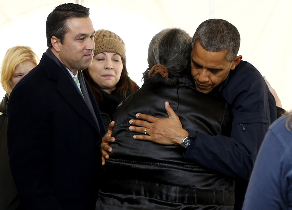Photo -   President Barack Obama hugs a woman as he visits the FEMA recovery center on the grounds of New Dorp High School, Thursday, Nov. 15, 2012 on Staten Island, in New York. At left is Rep. Michael Grimm, R-N.Y. (AP Photo/Carolyn Kaster)