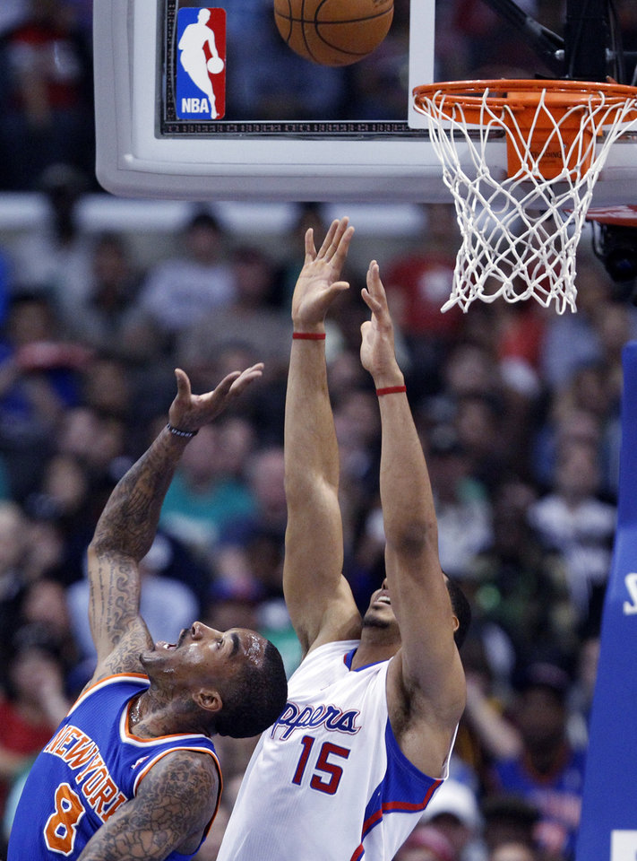 New York Knicks guard J.R. Smith (8) shoots as Los Angeles Clippers center Ryan Hollins (15) defends in the first half of an NBA basketball game in Los Angeles Sunday, March 17, 2013. (AP Photo/Reed Saxon)