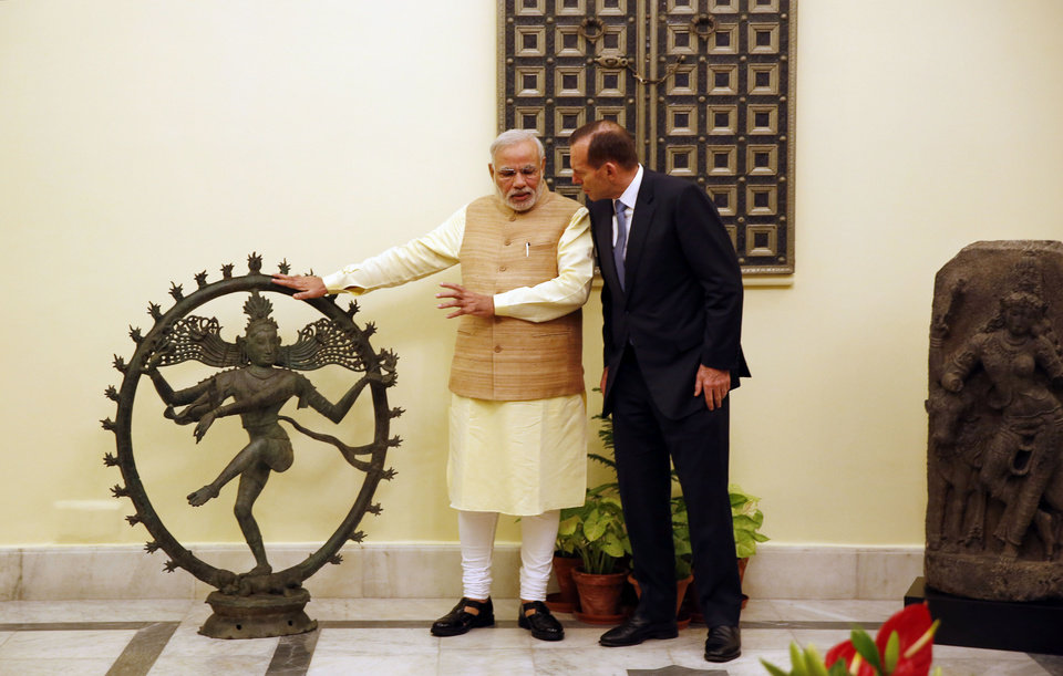 Photo - Indian Prime Minister Narendra Modi holds a bronze Nataraja idol handed over by his Australian counterpart Tony Abbott, right, in New Delhi, India, Friday, Sept. 5, 2014. Two idols, including the Nataraja idol, that were stolen from India and housed in Australian galleries were returned during Abbott's visit to the country. (AP Photo/Manish Swarup)