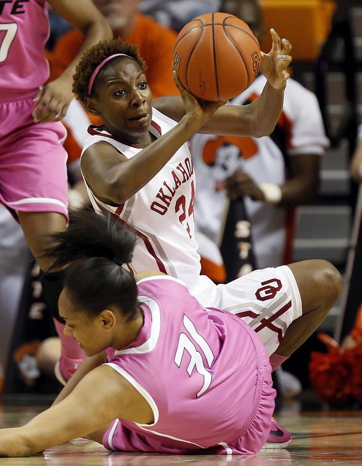 Photo - Oklahoma's Sharane Campbell (24) passes the ball away from Oklahoma State's Kendra Suttles (31) in the first half during the women's Bedlam college basketball game between the OU Sooners and the OSU Cowgirls at Gallagher-Iba Arena in Stillwater, Okla., Sunday, Feb. 16, 2014. Photo by Nate Billings, The Oklahoman