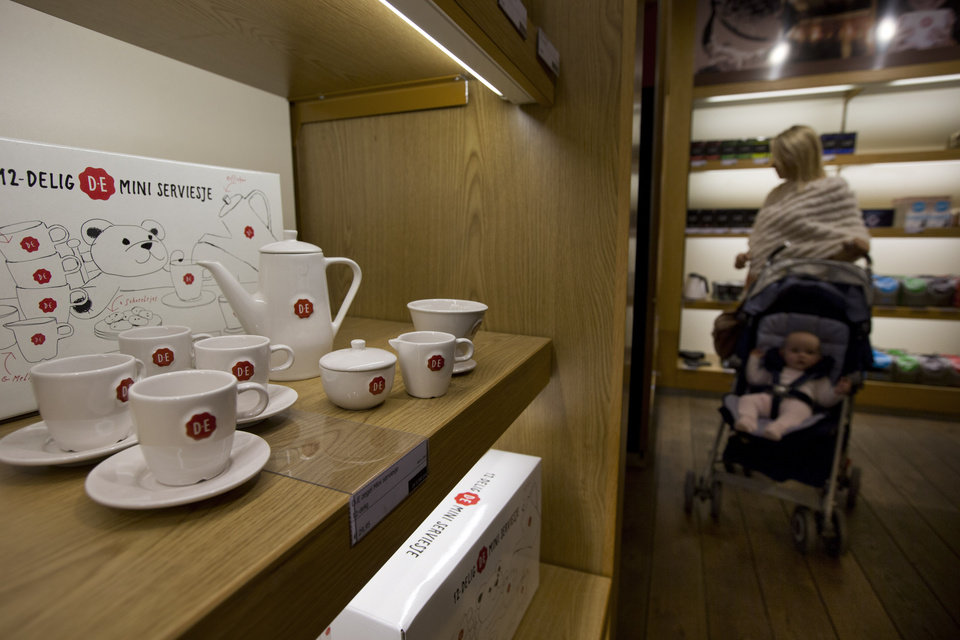 Photo - A woman with a baby stroller shops at Douwe Egberts Café as a mini coffee set with the D.E. company logo is displayed in the store in Villa ArenA interior design mall on the outskirts of Amsterdam, Netherlands, Wednesday, May 7, 2014. Mondelez International Inc. and D.E. Master Blenders 1753 B.V. are combining their coffee businesses. The business will house coffee brands such as Gevalia and Jacobs from Mondelez and Senseo and Douwe Egberts from D.E. Master Blenders, formerly the Sara Lee coffee business. The new company will be called Jacobs Douwe Egberts and be headquartered in the Netherlands. The combined company will have annual revenue of more than 7 billion U.S. dollars. (AP Photo/Peter Dejong)