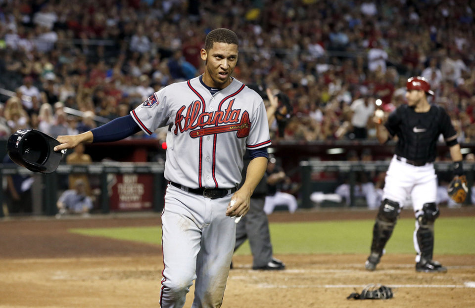 Photo - Atlanta Braves' Andrelton Simmons waves to a teammate with his helmet after he scored a run, as Arizona Diamondbacks' Miguel Montero, right, talks with the umpire about the call at home during the third inning of a baseball game Saturday, June 7, 2014, in Phoenix. (AP Photo/Ross D. Franklin)