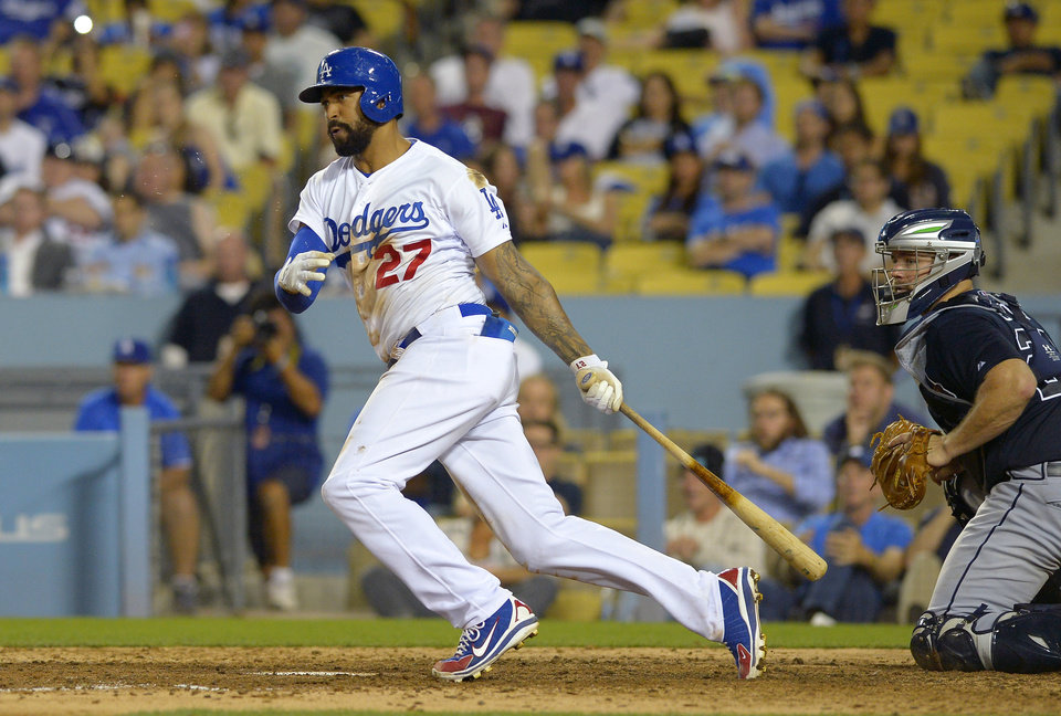 Photo - Los Angeles Dodgers' Matt Kemp, left, hits an RBI single to win the game as Atlanta Braves catcher Evan Gattis looks on during the 10th inning of a baseball game, Wednesday, July 30, 2014, in Los Angeles. (AP Photo/Mark J. Terrill)