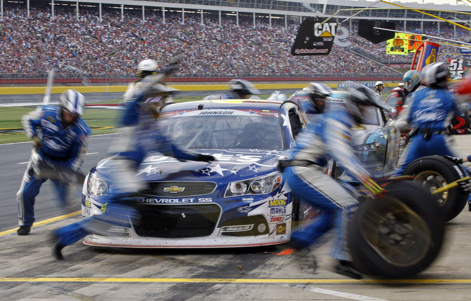 Photo - In this photo taken at a slow shutter speed crew members perform a pit stop on driver Jimmie Johnson's car during the NASCAR Sprint Cup series Coca-Cola 600 auto race at Charlotte Motor Speedway in Concord, N.C., Sunday, May 25, 2014. (AP Photo/Terry Renna)
