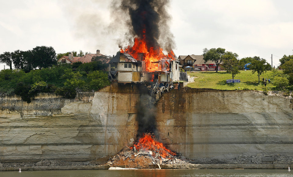 Photo - A gated community White Bluff home is burned to save Lake Whitney from falling debris Friday June 13, 2014 in Lake Whitney, Texas. The White Bluff home is built on a fault line and is gradually collapsing with the cliff side into the lake. (AP Photo/The Fort Worth Star-Telegram, Ron Jenkins) MAGS OUT (FORT WORTH WEEKLY, 360 WEST); IINTERNTET OUT