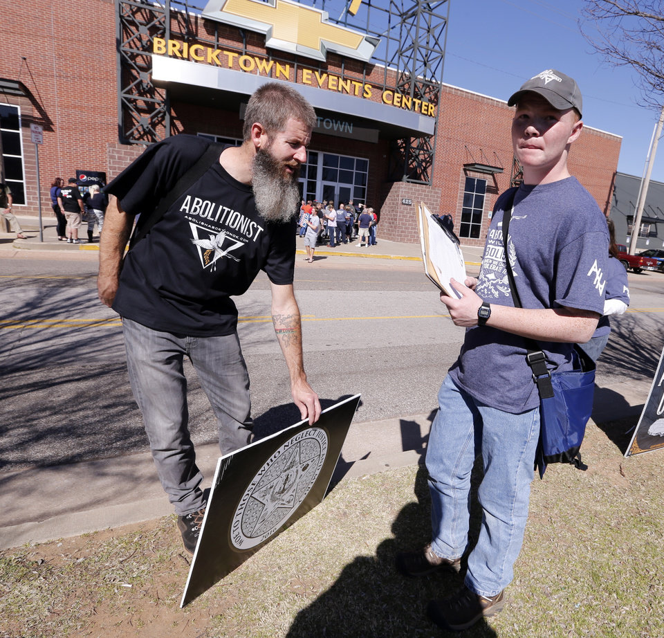 Photo - Toby Harmon, left, and others set up anti-abortion signs across the street as Republican presidential candidate Ted Cruz is scheduled to come to the Chevy Bricktown Event Center on Sunday, Feb. 28, 2016 in Oklahoma City, Okla.  Photo by Steve Sisney, The Oklahoman