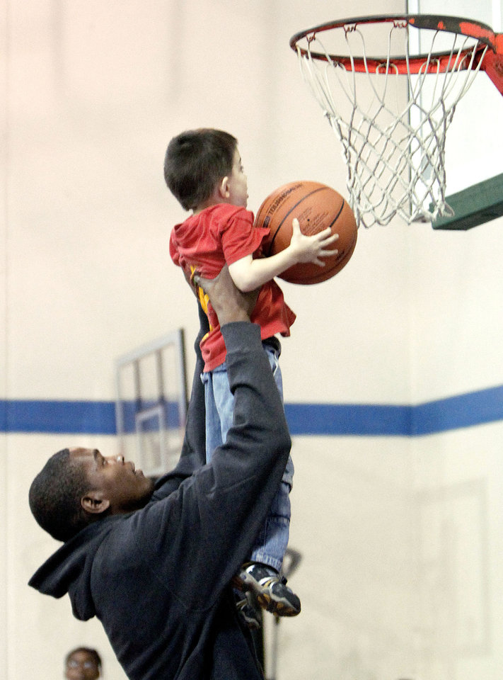 Oklahoma City Thunder player Kevin Durant helps Jared Blalack dunk a ball during the Nike Clinic at the Salvation Army Boy and Girls  Club, Saturday, Feb. 7, 2009, in Oklahoma City. PHOTO BY SARAH PHIPPS, THE OKLAHOMAN