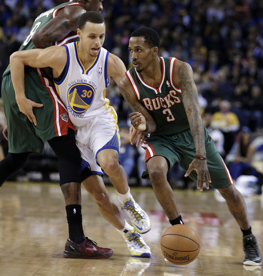 Milwaukee Bucks' Brandon Jennings, right, drives the ball past Golden State Warriors' Stephen Curry (30) during the first half of an NBA basketball game Saturday, March 9, 2013, in Oakland, Calif. (AP Photo/Ben Margot)