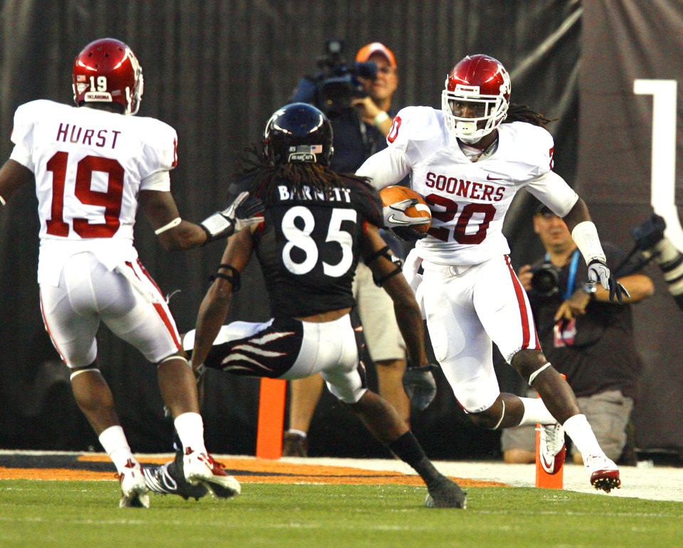 Photo - Quinton Carter (20) intercepts a pass from DJ Woods (3) on a reverse/pass play as OU's Demontre Hurst blocks during the first half of the college football game between the University of Oklahoma Sooners (OU) and the University of Cincinnati Bearcats (UC) at Paul Brown Stadium on Saturday, Sept. 25, 2010, in Cincinnati, Ohio.   Photo by Steve Sisney, The Oklahoman