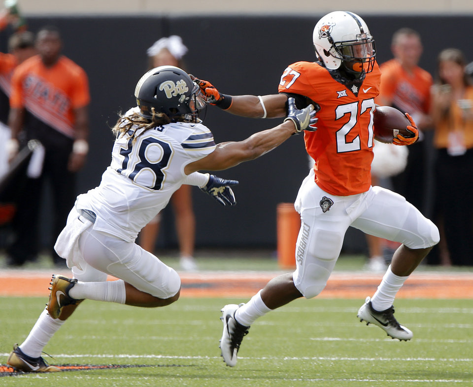 Photo - Oklahoma State's Justice Hill (27) stiff arms Pittsburgh's Ryan Lewis (38) during a college football game between the Oklahoma State Cowboys (OSU) and the Pitt Panthers at Boone Pickens Stadium in Stillwater, Okla., Saturday, Sept. 17, 2016. Photo by Chris Landsberger, The Oklahoman