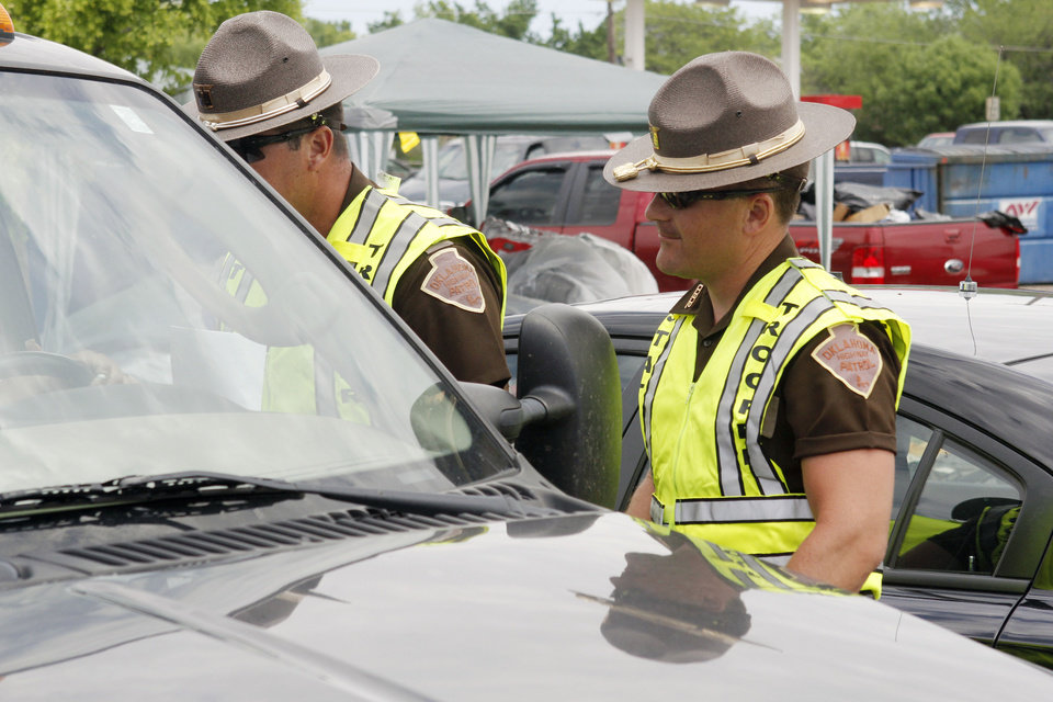 Photo - Highway Patrol troopers Randall Milan, left, and Gabe Leach work perimeter security on the north side of the tornado devestated part of Moore, OK, Thursday, May 23, 2013,  Photo by Paul Hellstern, The Oklahoman