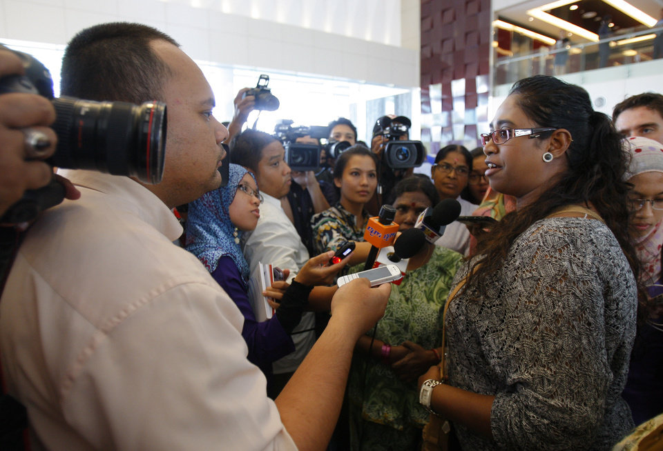 Photo - A family member of passengers aboard a missing Malaysia Airlines plane speaks to journalists at a hotel in Putrajaya, Malaysia, Monday, March 10, 2014. Vietnamese aircraft spotted what they suspected was one of the doors of the missing Boeing 777 on Sunday, while questions emerged about how two passengers managed to board the ill-fated aircraft using stolen passports. (AP Photo/Lai Seng Sin)