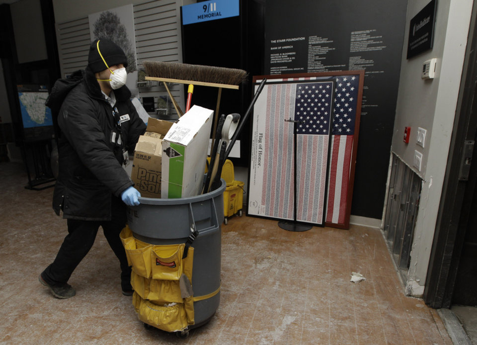 "A 9-11 Memorial worker wheels clean-up equipment through the World Trade Center Memorial visitor center late Monday as work continues to get it up and running after it was damaged by flooding from Superstorm Sandy, Monday, Nov. 5, 2012, in New York. The World Trade Center Memorial will re-open to the public Tuesday. Parts of the visitor center and a special room for victims' families were damaged by four feet of water, as was some of the museum that is being built. But ""the most sacred"" point of the memorial remains intact the reflective fountains ringed by the names of the dead. (AP Photo/Kathy Willens)"