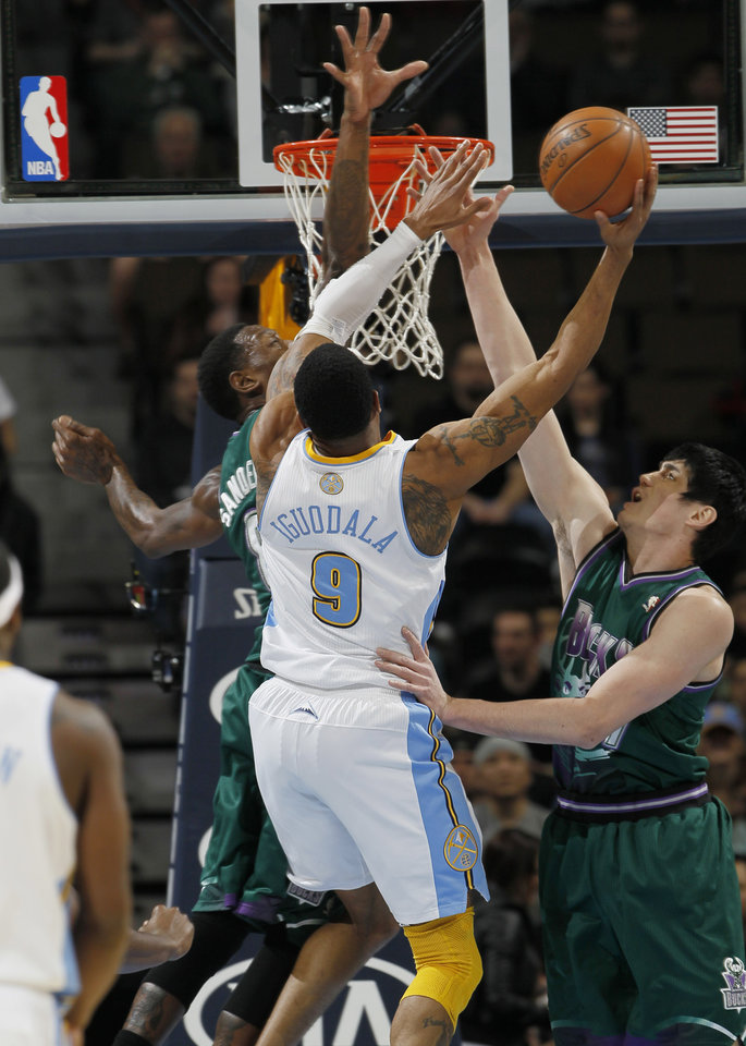 Photo - Denver Nuggets guard Andre Iguodala, center, tries to drive for a shot as Milwaukee Bucks center Larry Sanders, left, and forward Ersan Ilyasova, right, of Turkey, defend during the first quarter of an NBA basketball game in Denver on Tuesday, Feb. 5, 2013. (AP Photo/David Zalubowski)