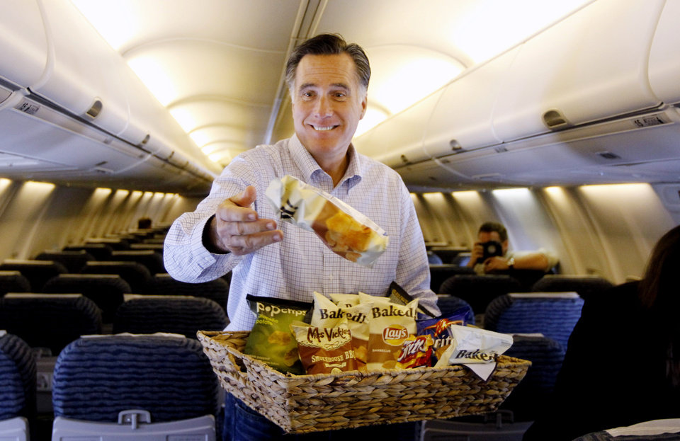 Photo -   Republican presidential candidate, former Massachusetts Gov. Mitt Romney throws bags of chips at traveling reporters on his campaign charter plane in Jacksonville, Fla., Monday, Jan. 30, 2012. (AP Photo/Charles Dharapak)